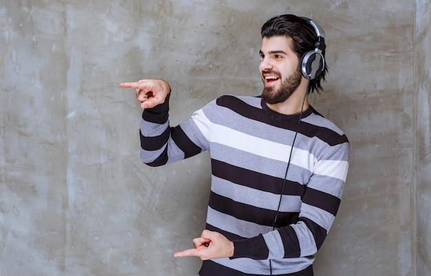 Man met koptelefoon die de grootte van een object laat zien