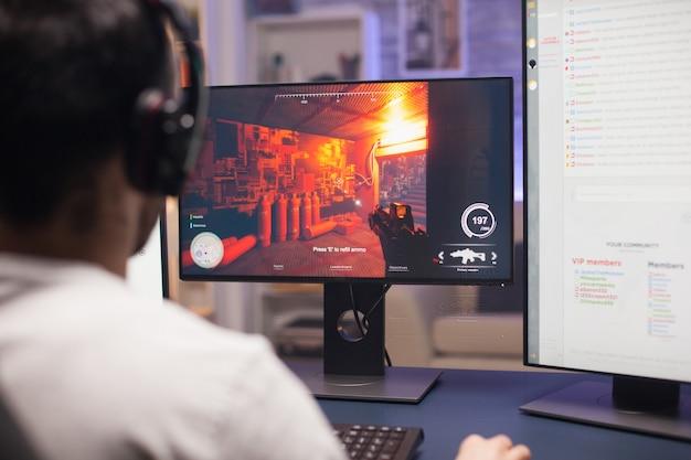 Man met koptelefoon die schietspel speelt op stream met behulp van krachtige computer.