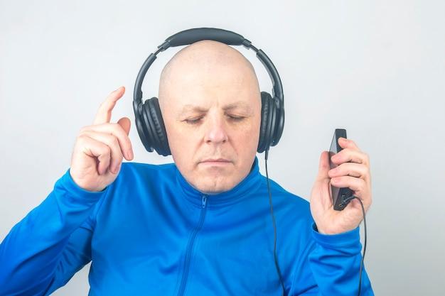 Man met koptelefoon en digitale draagbare speler in handen in ontspanning tijdens het luisteren naar zijn favoriete muziek