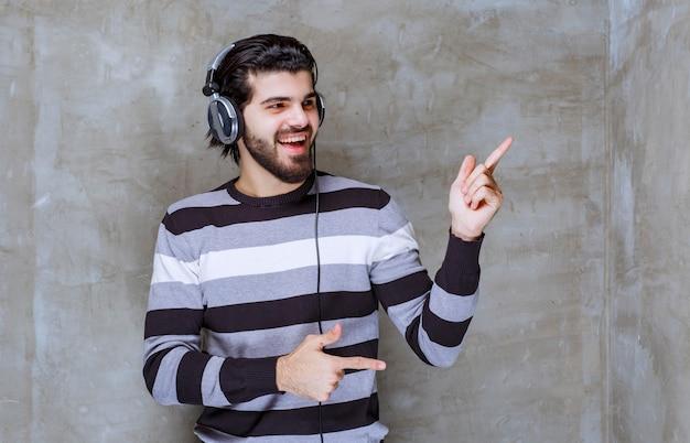 Man met koptelefoon interactie met iemand terzijde