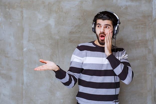 Man met koptelefoon kijkt verbaasd en doodsbang
