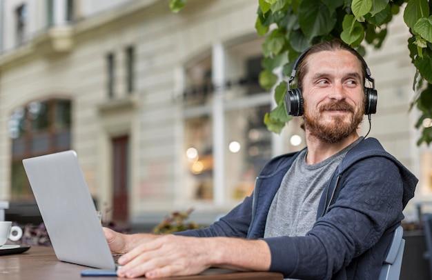 Man met koptelefoon op een terras van de stad met laptop