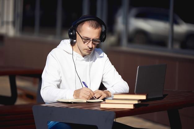 Man met koptelefoon werkt op een laptop en schrijft in een notitieblok zittend op straat aan een tafel. sociale afstand nemen tijdens het coronavirus