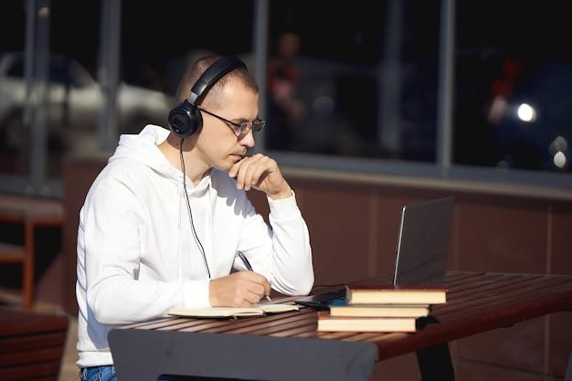 Man met koptelefoon werkt op een laptop en schrijft in een notitieblok zittend op straat aan een tafel sociale afstand nemen tijdens het coronavirus