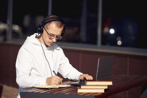 Man met koptelefoon werkt op een laptop en schrijft in een notitieblok zittend op straat aan een tafel