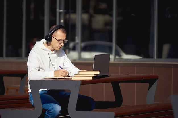 Man met koptelefoon werkt op een laptop en schrijft in een notitieblok