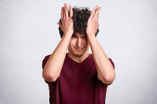 Man met krullend haar, draagt casual kastanjebruin t-shirt, heeft ongelukkige uitdrukkingen, raakt zijn hoofd met handen geïsoleerd op wit. kopieer ruimte voor uw advertentie of promotietekst.