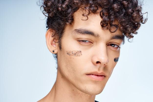 Man met krullend haar en zwarte crème zoals oorlogsverf geïsoleerd op een witte achtergrond