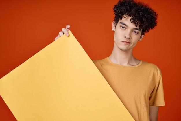 Man met krullend haar gele poster in handen reclame