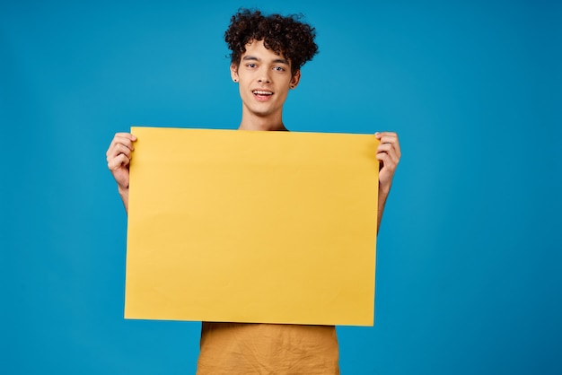 Man met krullend haar gele poster mockup reclame blauwe achtergrond