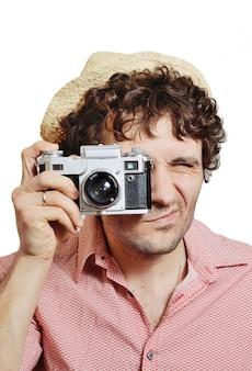Man met krullend haar in een hoed met een vintage camera neemt foto's