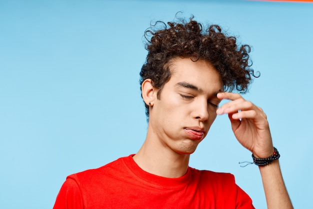 Man met krullend haar in een rode t-shirt grimas leuke telefoon. hoge kwaliteit foto