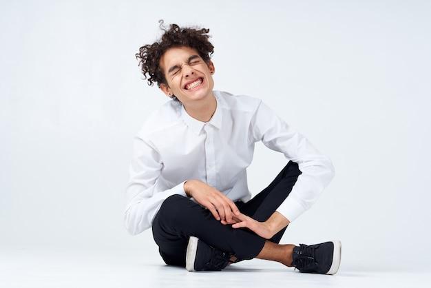 Man met krullend haar in een wit overhemd, sneakers en broek zit op de grond