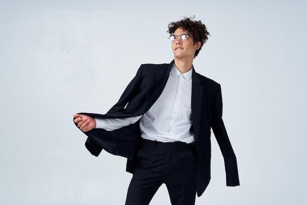 Man met krullend haar in zwart pak in studio