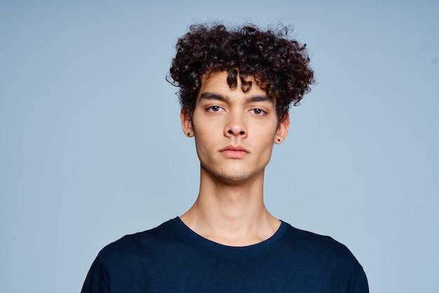 Man met krullend haar in zwarte t-shirt bijgesneden weergave geïsoleerd