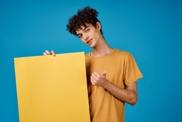 Man met krullend haar met een gele poster in zijn handen reclame. hoge kwaliteit foto