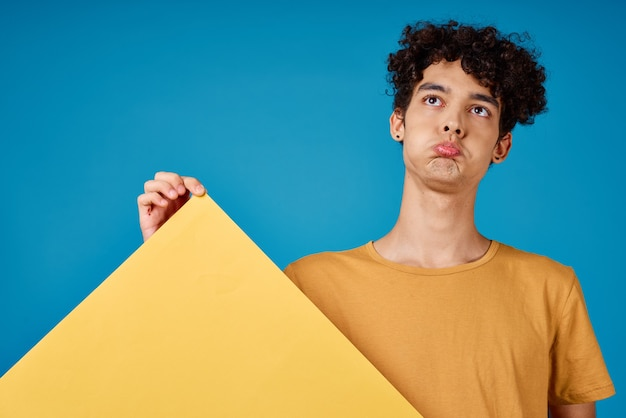 Man met krullend haar met gele poster grimas blauwe achtergrond