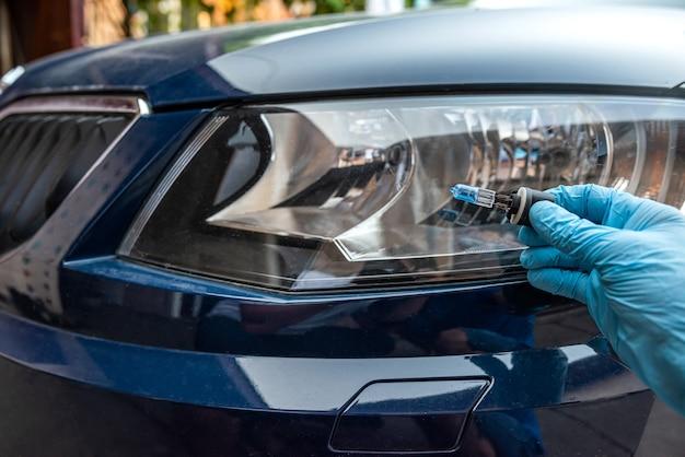 Man met lamp voor reparatie auto licht, koplamp