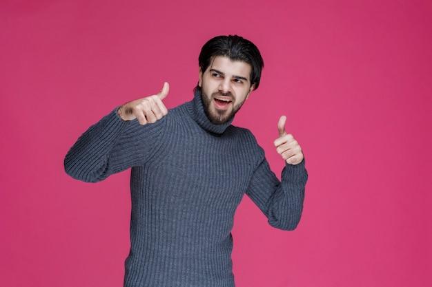 Man met lang haar en baard duim omhoog handteken maken.