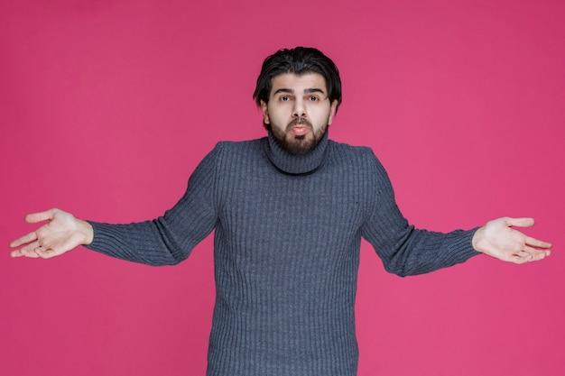 Man met lang haar en baard opent zijn handen en ziet er verward of onervaren uit.