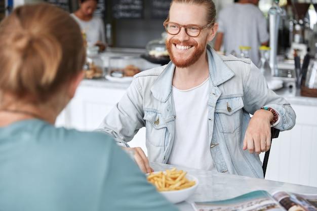 Man met lang haar, gekleed in modieuze spijkerjasje in café