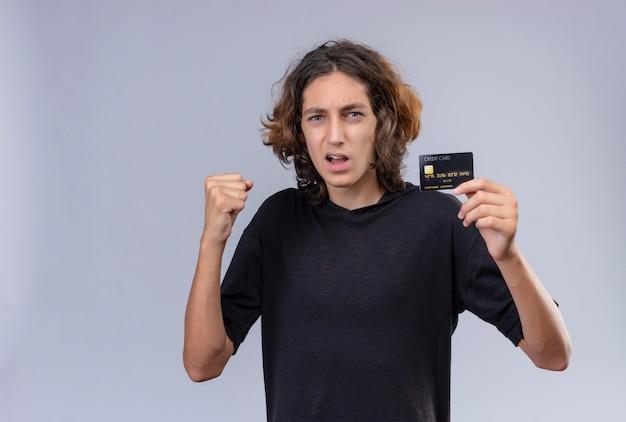 Man met lang haar in zwart t-shirt met een bankkaart op een witte muur