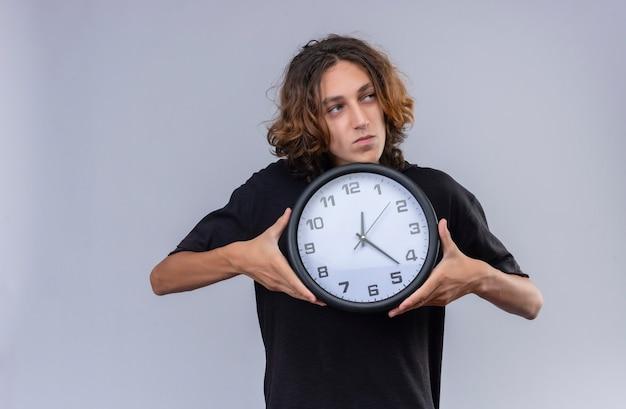 Man met lang haar in zwart t-shirt met een wandklok op een witte muur