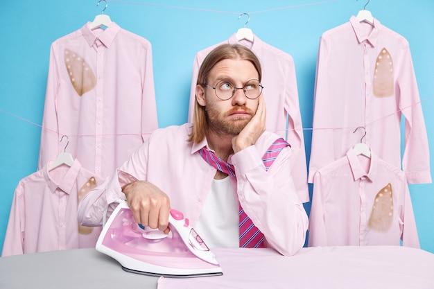 Man met lang rood haar en baard denkt wat te dragen voor speciale gelegenheden strijkt kleren gebruikt elektrisch strijkijzer draagt bril overhemd en stropdas om nek blauw