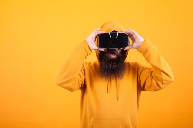 Man met lange baard met een virtual reality-headset die geschokt kijkt over gele achtergrond. gele hoodie. moderne technologie. knappe man.