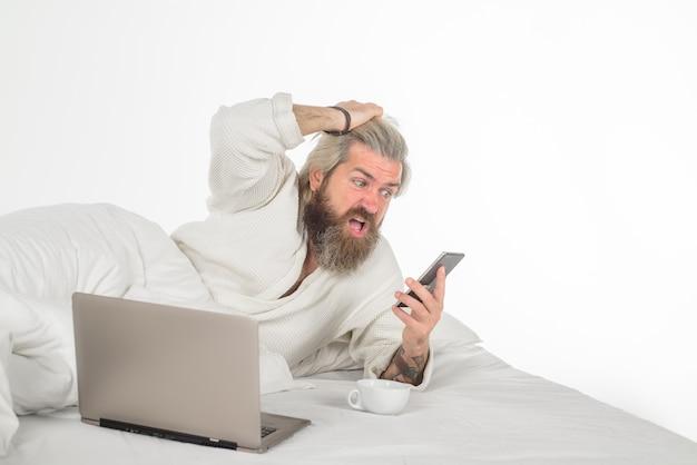 Man met laptop aan het werk in bed zelfisolatie werk vanuit huis man met laptop en smartphone