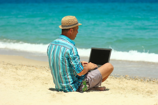 Man met laptop aan zee in de zomer concept voor werken op afstand
