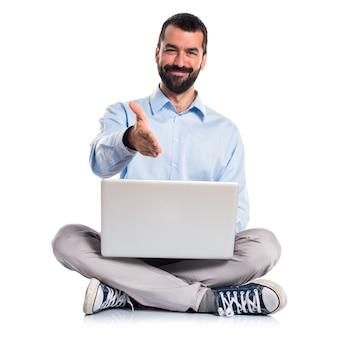 Man met laptop die een deal maakt