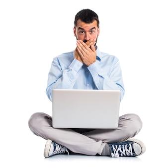 Man met laptop die zijn mond bedekt