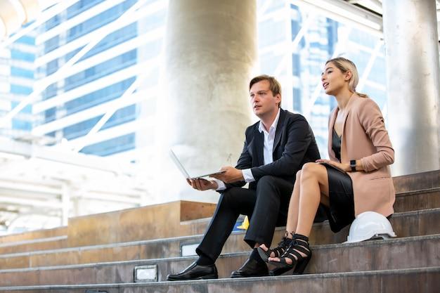 Man met laptop door vrouw die digitale tablet houden terwijl het zitten op trap