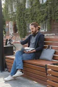Man met laptop en hoofdtelefoon buitenshuis in de stad