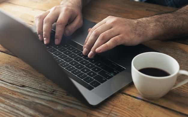 Man met laptop in het kantoor aan huis mannelijke handen typen op toetsenbord