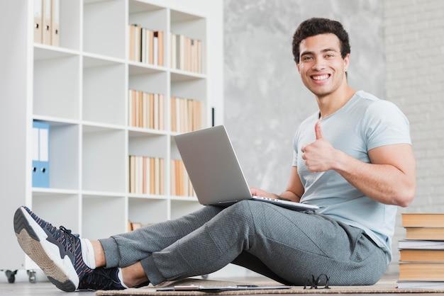 Man met laptop omringd door boeken