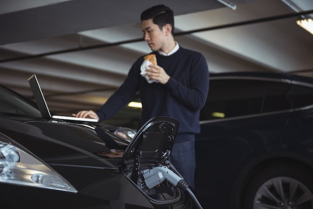 Man met laptop tijdens het opladen van elektrische auto