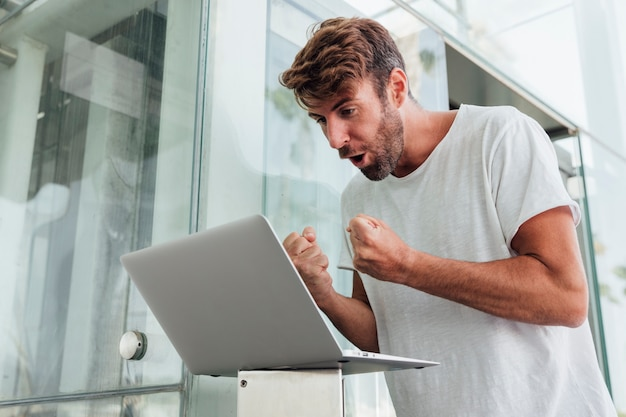 Man met laptop vieren met vuisten