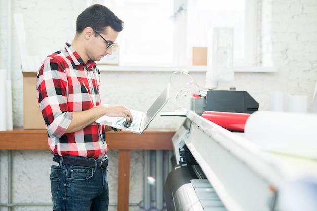 Man met laptop werken in drukkerij