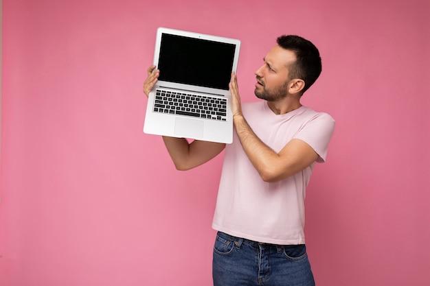 Man met laptopcomputer kijken naar netbook scherm in t-shirt op geïsoleerde roze achtergrond.