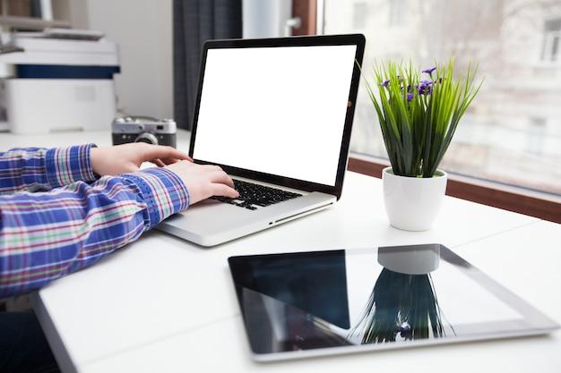 Man met laptopcomputer naast een venster van de stad met tablet pc en een retro camera op een tafel