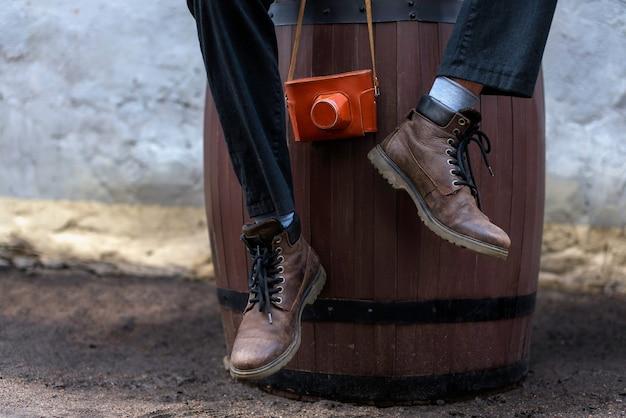 Man met lederen laarzen zittend op een houten vat en vintage filmcamera te houden