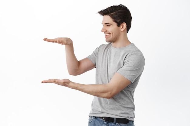 Man met lege ruimte en glimlachen, kijkend naar item in zijn handen met een blij gezicht, blij tegen de witte muur staan