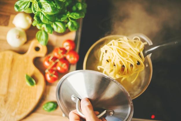 Man met lepel met stomende pasta