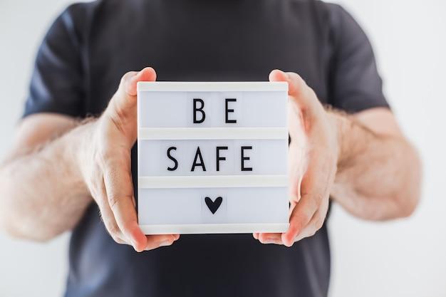 Man met lightbox met tekst wees veilig