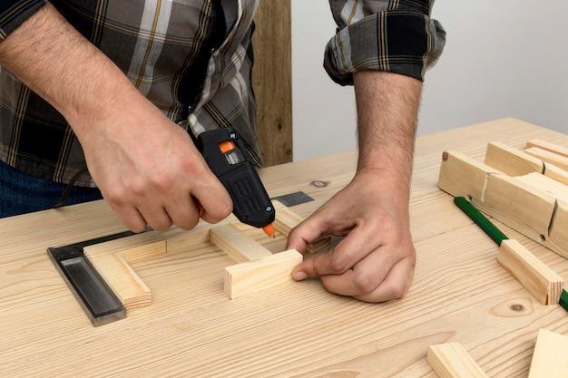 Man met lijm op hout timmerwerk workshop concept