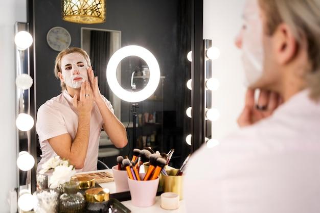 Man met make-up een gezichtsmasker in de spiegel toe te passen