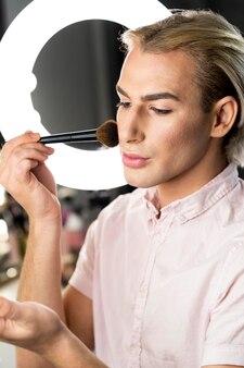 Man met make-up en naar beneden te kijken