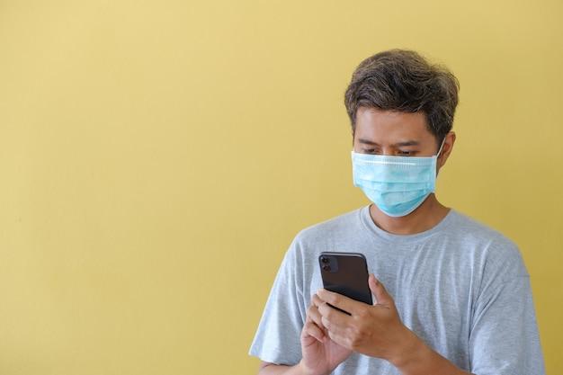 Man met masker en met behulp van mobiele telefoon op yello